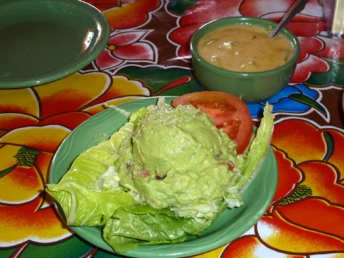 Guacamole in the foreground; Chili con Queso with green chili strips behind