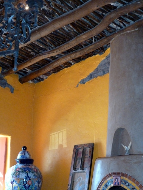 The 1800s adobe peeking through from beneath viga ceiling