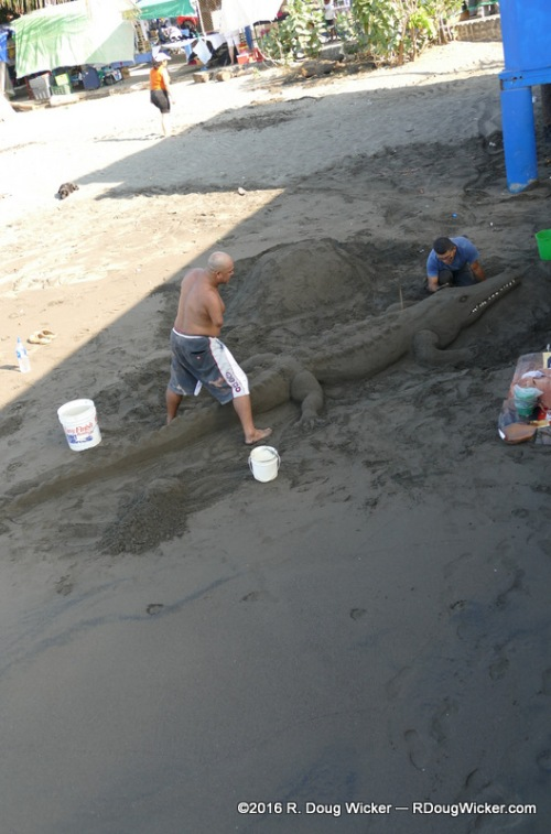 Sand sculptors alongside the dock