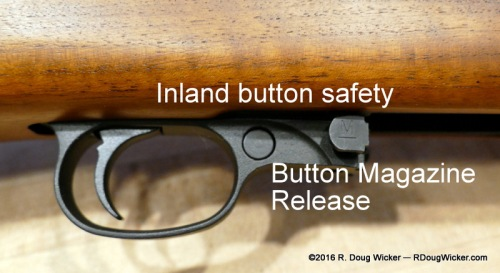 Inland push-button safety (depressed) next to the magazine release button